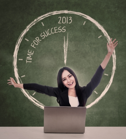 Businesswoman with laptop cheering for success in year 2013 photo