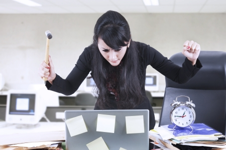 office chaos: Young businesswoman is getting impatient while holding hammer in front of her laptop in office