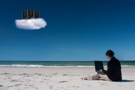 Businesswoman with her laptop sitting on the beach under server cloud photo