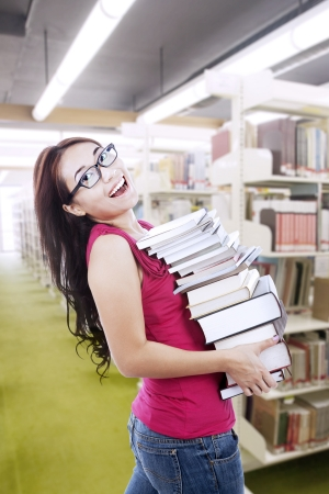Female student is happily carrying books to study for her exams photo