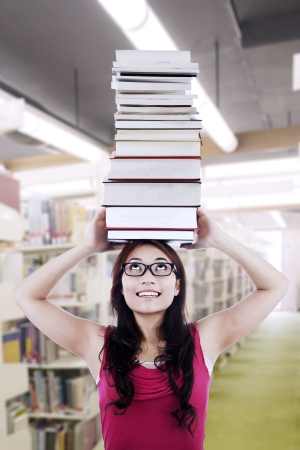 A beautiful nerd girl student wearing glasses is holding stack of books on top of her head photo