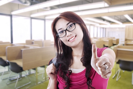 A girl student with glasses showing thumb up in the classroom photo