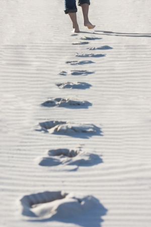 Footprints of a girl walking on the sand at the beach photo