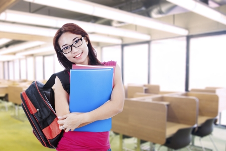 secondary school student: Happy female student carrying a bag and folder at school