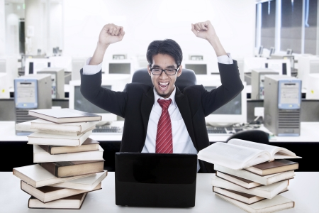 Young businessman raised his arms due to successful project photo