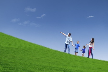 kid pointing: Happy family walking on the hill to see beautiful landscape