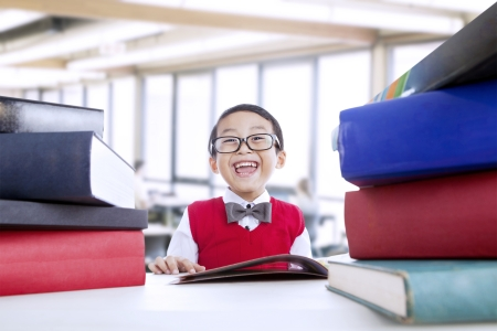 elementary school student: Happy boy is studying at the library surrounded with books Stock Photo