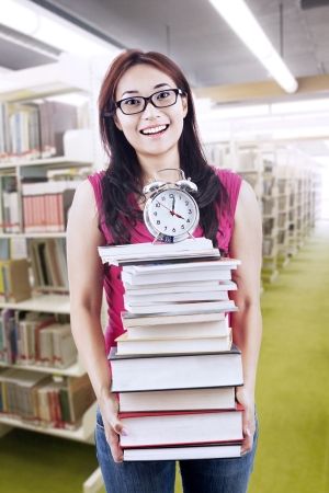 Young female student carrying stack of books with a clock on top photo