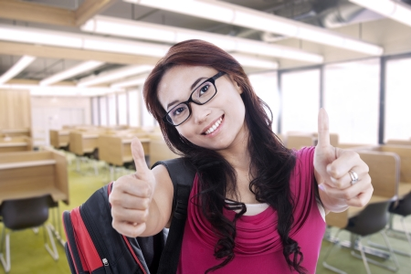 Happy female student with thumbs up in classroom photo