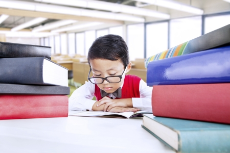 Cute nerd boy surrounded with books while studying in the library photo