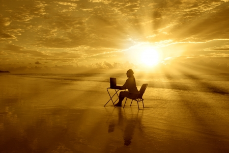La muchacha está sentada con su computadora portátil bajo el hermoso atardecer en la playa