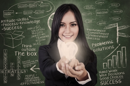 Businesswoman give light bulb in classroom with blackboard background Stock Photo - 16823452