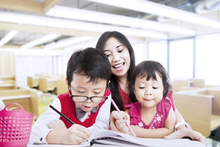 asian teacher: Mother teaches her children to be creative in drawings Stock Photo