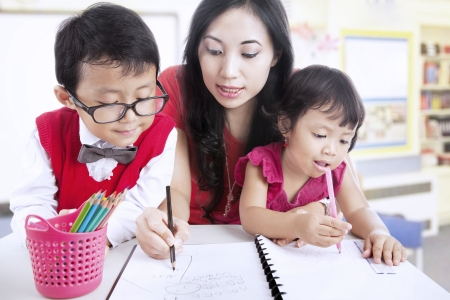 teaches: Beautiful mother teaches her children to write in class