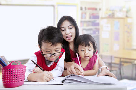 Teacher and children study in classroom together photo