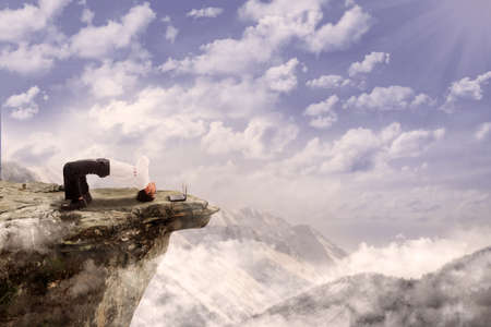 nature photography: Businessman doing acrobatic while working with his laptop on top of a mountain Stock Photo