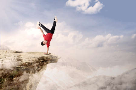 A guy is doing cartwheel acrobatic on mountain high photo