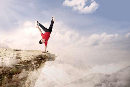 challange: A guy is doing cartwheel acrobatic on mountain high
