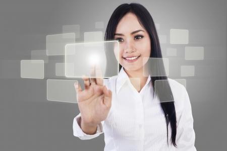 美しい女性実業家は灰色の背景上 copyspace で何かをタッチします。