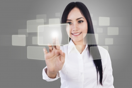 touch screen computer: Beautiful businesswoman touch something on copyspace over grey background Stock Photo