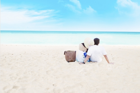 seasides: Young couple sitting together on beach. shot at tropical beach Stock Photo