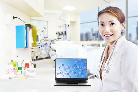 Beautiful scientist smiling while showing her laptop at the hospital photo