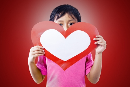 A boy is holding a blank love card on red background photo
