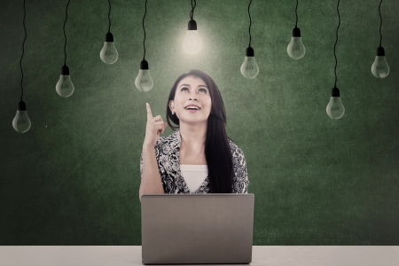 Businesswoman looking at lit light bulb in front of laptop photo