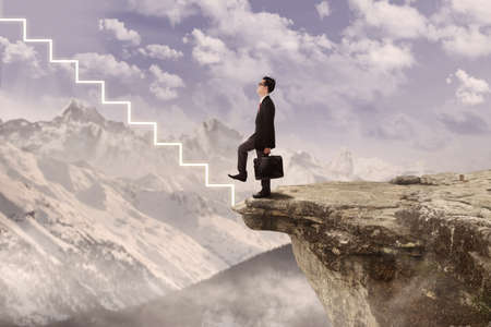 cliff edge: Businessman is walking up the virtual stairs from the edge of a mountain