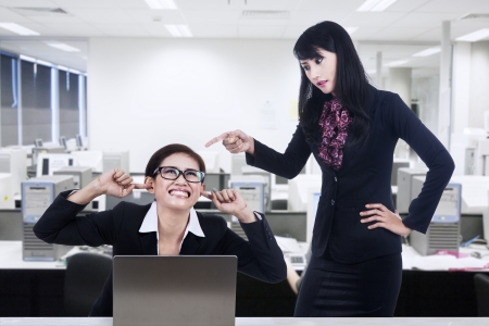 using voice: Young businesswoman is shouting at her subordinate Stock Photo