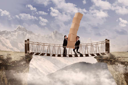 top of mountain: Teamwork concept showing two businessmen carrying pile of boxes