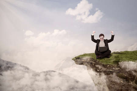 Picture of businessman with arms raised while sitting with his laptop on a mountain high photo