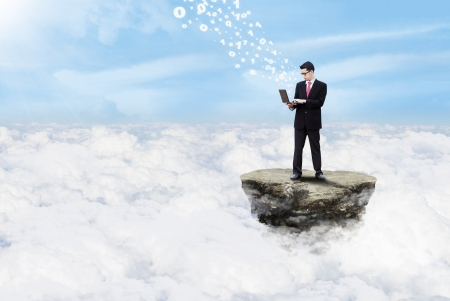 Young businessman working with his laptop above clouds on top of a rock Stock Photo - 17249645