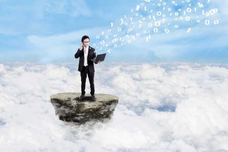 Young businessman holding laptop while standing on a rock, above the clouds photo
