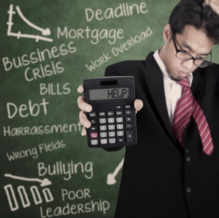Businessman is showing calculator with HELP writing on it in front of blackboard photo