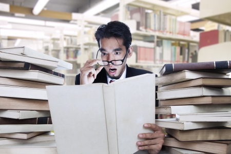 Businessman looking a white book on shock at the library photo