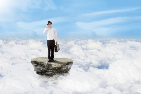 Young businessman is carrying a bag while calling above the clouds Stock Photo - 17249647
