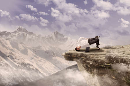 Businessman with laptop is doing acrobatic on top of a mountain Stock Photo - 17249724