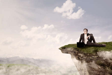 Young businessman is sitting with his laptop on top of a mountain photo