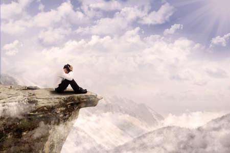 Jeune homme d'affaires est assis avec sa t�te vers le bas sur le bord de la montagne photo