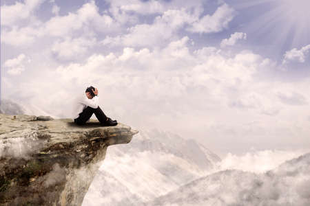 Young businessman is sitting with his head down on the edge of the mountain photo