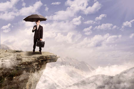 Young businessman holding umbrella while standing on top of a mountain photo