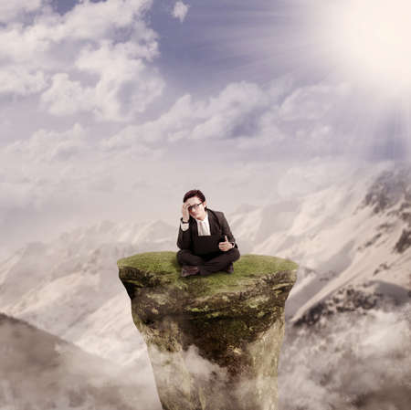 blue sky thinking: Picture of thinking businessman sitting with his laptop on a mountain rock