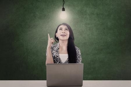 Hermosa mujer de negocios bajo una bombilla encendida mientras trabaja con su computadora portátil