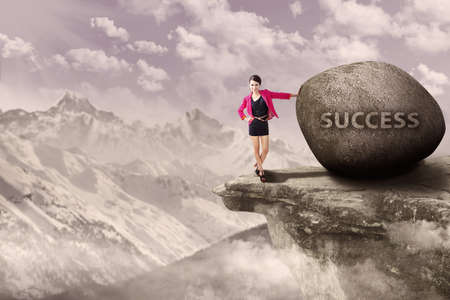 Young businesswoman standing next to rock of success on top of a mountain Stock Photo - 17249735