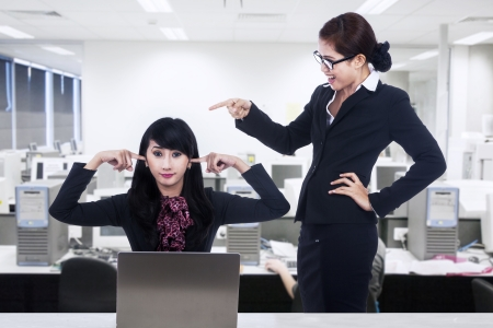 using voice: A businesswoman is bullying her subordinate in the office