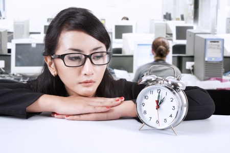 Beautiful businesswoman looking at a clock photo