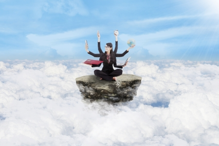 Young businesswoman multitasking above the clouds photo