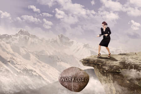 Businesswoman is pulling Loan rock on top of a mountain photo