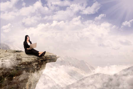 Young businesswoman is relaxing while working with her laptop on a mountain photo
